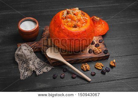 Pumpkin risotto with raisins. Rice porridge with sweet pumpkin raisins nuts. Baked pumpkin Halloween for rice. Sugar dark wooden background.