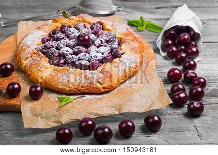 Open pie tart dough sprinkled powdered sugar with ripe cherries on paper on board fresh cherry in white paper bags red cherry for pie tart on gray wooden background.