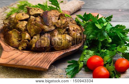 Stewed chicken liver additional ingredients for chicken liver parsley dill cherry tomatoes shallot gray wooden background rustic style