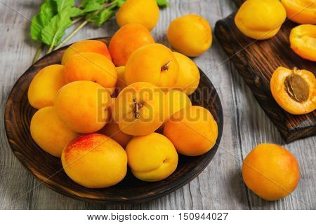 Fresh ripe apricots on wooden plate mint leaves fruits apricots on cutting board cut apricots in half. Light white rustic wood background.
