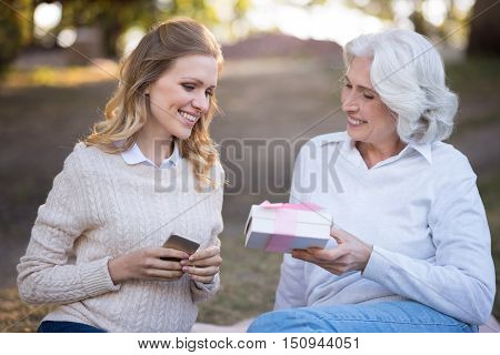 The best present ever. Gray haired beautiful woman smiling and holding present from her daughter while sitting on the ground.