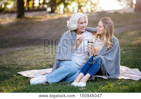 Outdoors conversation. Beautiful pleasant daughter and mother talking an eating cakes while sitting on the ground.