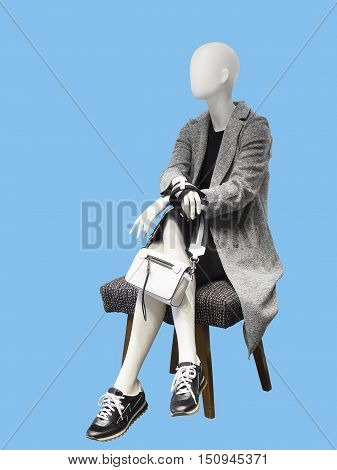 Sitting female mannequin wearing gray coat isolated on blue background. No brand names or copyright objects.