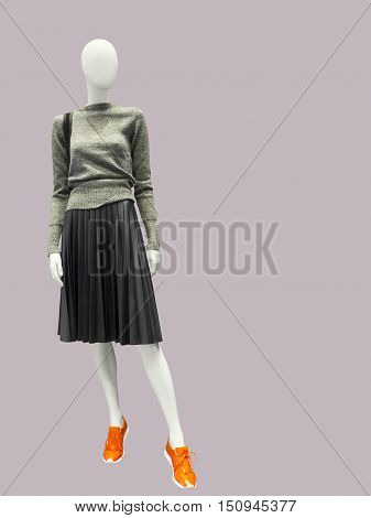 Full-length female mannequin dressed in gray sweater and skirt isolated. No brand names or copyright objects.