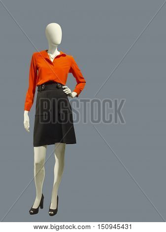 Full length female mannequin dressed in red blouse and black skirt over gray background. No brand names or copyright objects.
