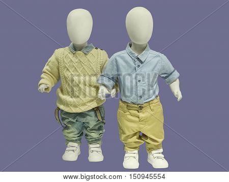 Two children mannequins dressed in a fall style. Isolated on gray background. No brand names or copyright objects.