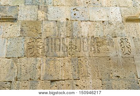 The wall of St Peter and Paul Basilica decorated with carved small carved khachkars (cross-stones) Tatev Monastery Syunik Province Armenia.