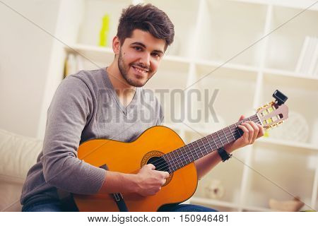 Young man playing guitar and composing a song