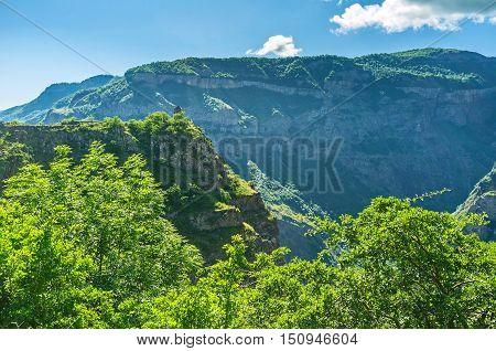 The medieval Bell Chapel on the steep rocky overlooks the mountains around deep Vorotan Gorge and Tatev Monastery Halidzor village Syunik Province Armenia.