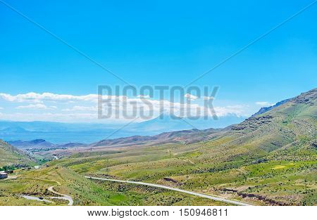 The mountain landscape of Ararat Province with the view on Ararat mountain topped with white clouds and covered with light haze Armenia.
