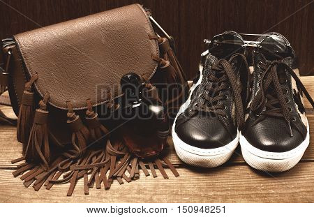 boots and brown bag on wooden table