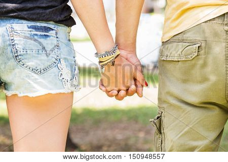 Friendship and love of man and woman - girl and guy hand in hand walking away in nature park - backside of two young guys in love - concept of romantic moment on honeymoon - summer outfit clothes