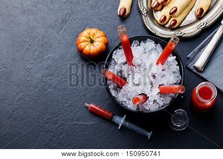 Cookies Witch's fingers with bloody cocktail for Halloween party celebration. Black stone background Copy space Top view