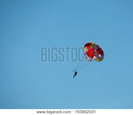 Parachute with man against a background of clear sky