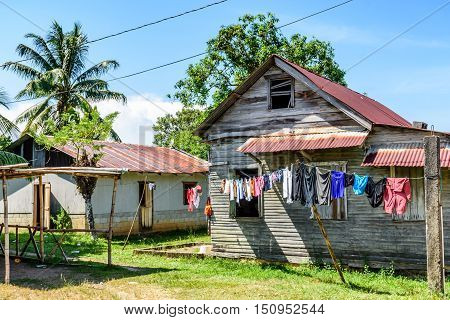 Laundry hangs on washing line outside wooden house in Caribbean town in Guatemala