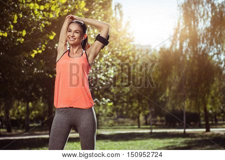 Stretching firstly. Beautiful cheerful happy girl in headphones preparing for her morning exercises and doing stretching while spending morning in the park.