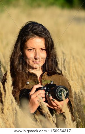 Portrait of young long haired brunette girl nature photographer in tall golden colored grass in the middle of autumn field ready in position for nice nature photos