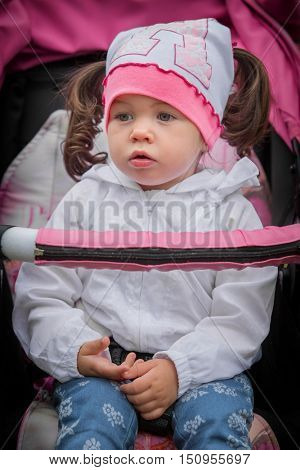 Little and very beautiful girl sitting in the pram