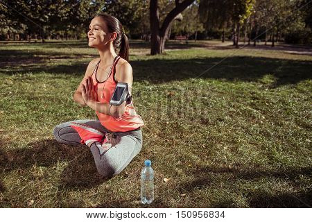 Stay calm. Pretty young concentrated girl doing yoga after having morning outdoors fitness and holding smartphone.