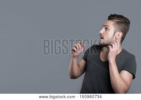 Our fears. Scared bearded young man opening his mouth and raising his hands while standing isolated in grey background
