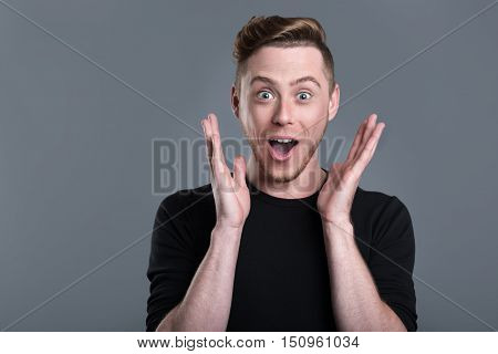 Pleasant news. Amazed bearded young man raising his hands to the open mouth while standing against grey background