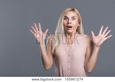 Overwhelmed with positive emotions. Amazed young woman raising her hands and opening her mouth while standing against grey background