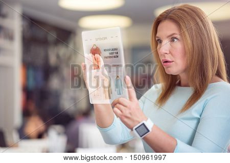 Advanced technologies in use. Pleasant beautiful surprised woman using tablet and expressing wonder while shopping online