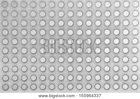 Perforated textured stell metallic background close up