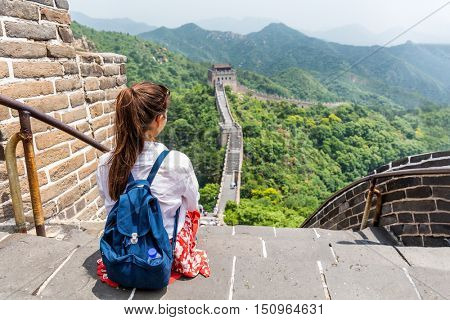 Great Wall of China. Tourist on Asia travel looking at Chinese landscape sitting relaxing on famous Chinese tourist destination and attraction in Badaling north of Beijing. Woman traveler on vacation.