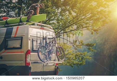 Ultimate RV Escape. Outdoor Men and His Camper Motorhome. Men Attaching His Kayak on the Camper Roof.