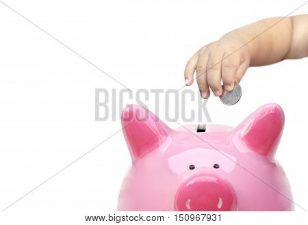 Hand of a young baby giving a silver coin to a piggy bank / Young generation start saving for the future