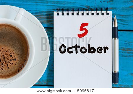 October 5th. Day 5 of month, tea or coffee cup with calendar on freelancer workplace background. Autumn time.
