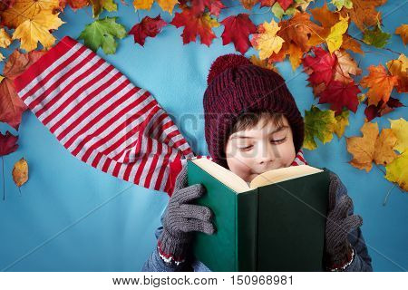 seven years old boy dreaming in autumn. Child in hat and scarf and maple leaves on blue background reading a book