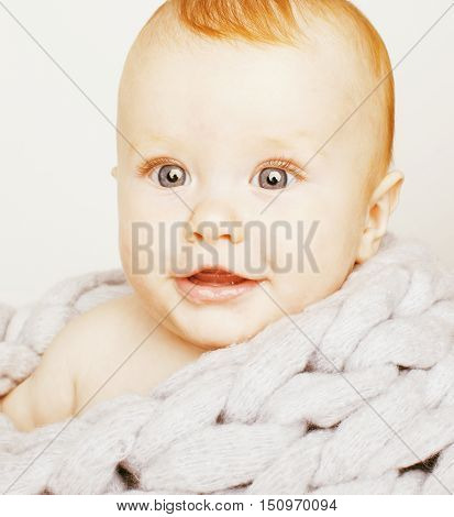 little cute red head baby in scarf all over him close up isolated, adorable kid winter cold concept
