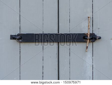Wrought Iron Door Latch on gray wooden building