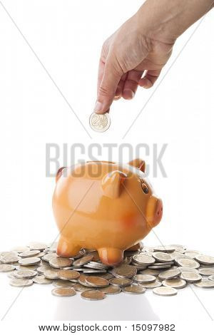 Female hand inserting a two Euros coin on a Piggy bank isolated over a white background