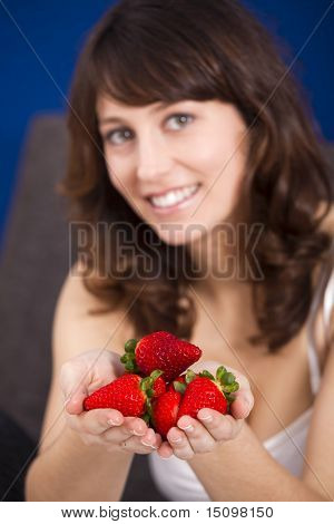 Beautiful and happy young woman with hands full of strawberries