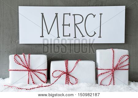 Label With French Text Merci Means Thank You. Three Christmas Gifts Or Presents On Snow. Cement Wall As Background. Modern And Urban Style. Card For Birthday Or Seasons Greetings.