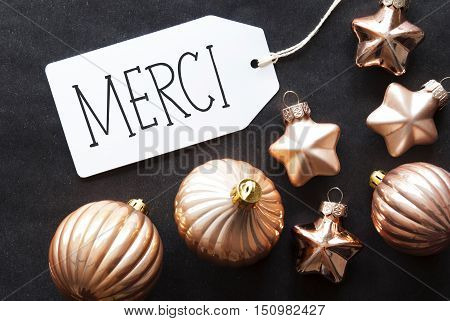 Label With French Text Merci Means Thank You. Bronze Christmas Tree Balls On Black Paper Background. Christmas Decoration Or Texture. Flat Lay View