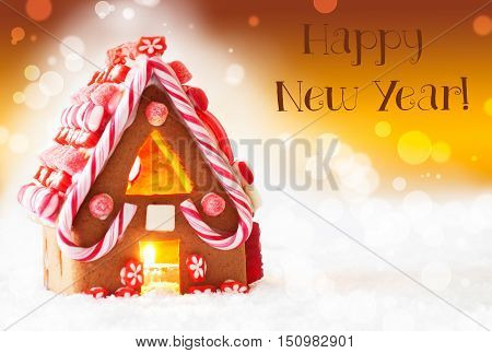 Gingerbread House In Snowy Scenery As Christmas Decoration. Candlelight For Romantic Atmosphere. Golden Background With Bokeh Effect. English Text Happy New Year