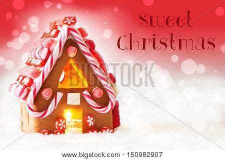 Gingerbread House In Snowy Scenery As Christmas Decoration. Candlelight For Romantic Atmosphere. Red Background With Bokeh Effect. English Text Sweet Christmas