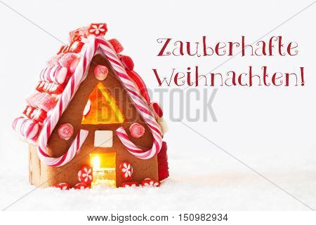 Gingerbread House In Snowy Scenery As Christmas Decoration With White Background. Candlelight For Romantic Atmosphere. German Text Zauberhafte Weihnachten Means Magic Christmas