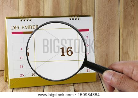 Magnifying glass in hand on calendar you can look Sixteenth date of monthFocus number sixteen in DecemberConcept in business and meetings.