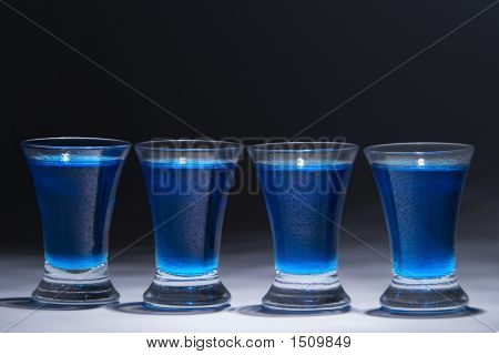 Blue Vodka In Four Glasses
