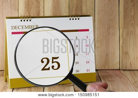 Magnifying glass in hand on calendar you can look Twenty Five date of monthFocus number Twenty Five in DecemberConcept in business and meetings.