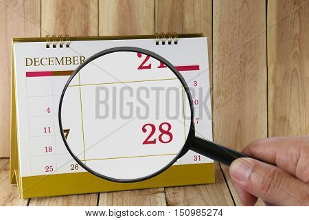 Magnifying glass in hand on calendar you can look Twenty-eight date of monthFocus number Twenty-eight in DecemberConcept in business and meetings.