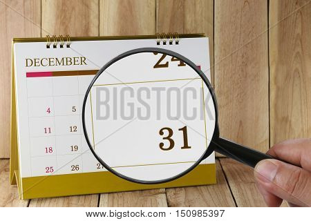 Magnifying glass in hand on calendar you can look thirty-one date of monthFocus number thirty one in DecemberConcept in business and meetings.