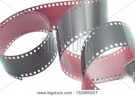 Curled up strip of film over white for concept about cinema making movies or 35mm photography