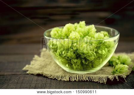 Close Up Of Green Ripe Hop Cones In A Glass Bowl Over Dark Rustic Wooden Background. Beer Production