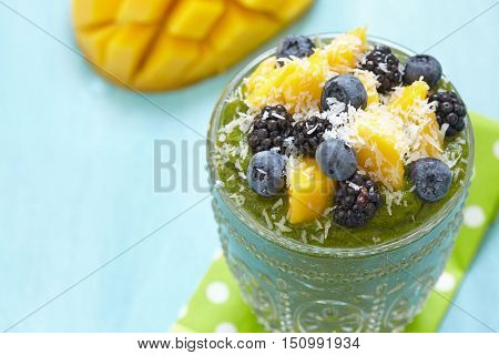 Breakfast green smoothie bowl topped with mango, bluebery and blackberry